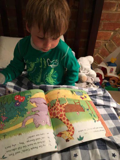 little boy reading in bed